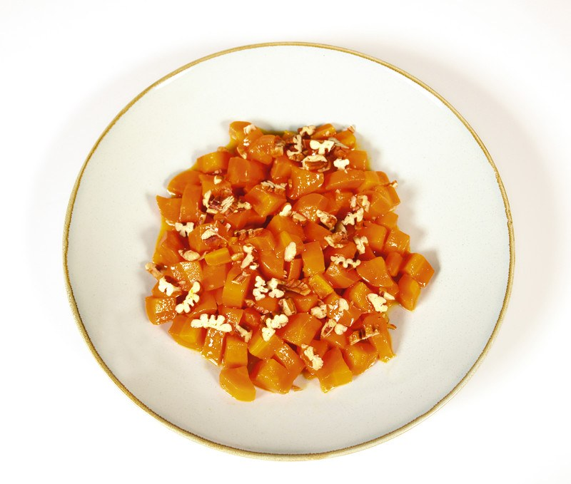 This photo shows an overhead view of a white plate of cooked diced carrots against a white background.