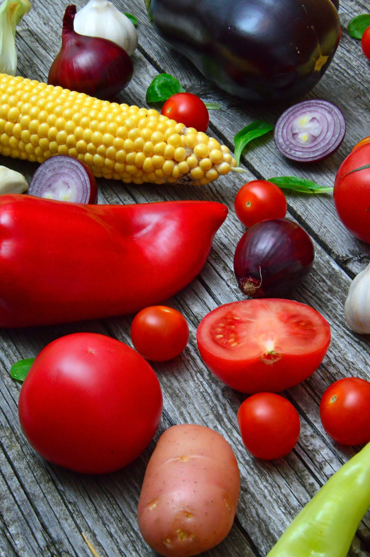 COLORFUL VEGETABLES SITTING ON A WOODEN TABLE INCLUDING, LARGE RED PEPPERS, RED ONION, TOMATOES, POTATO, GARLIC, CORN, BASIL LEAVES, AND EGGPLANT