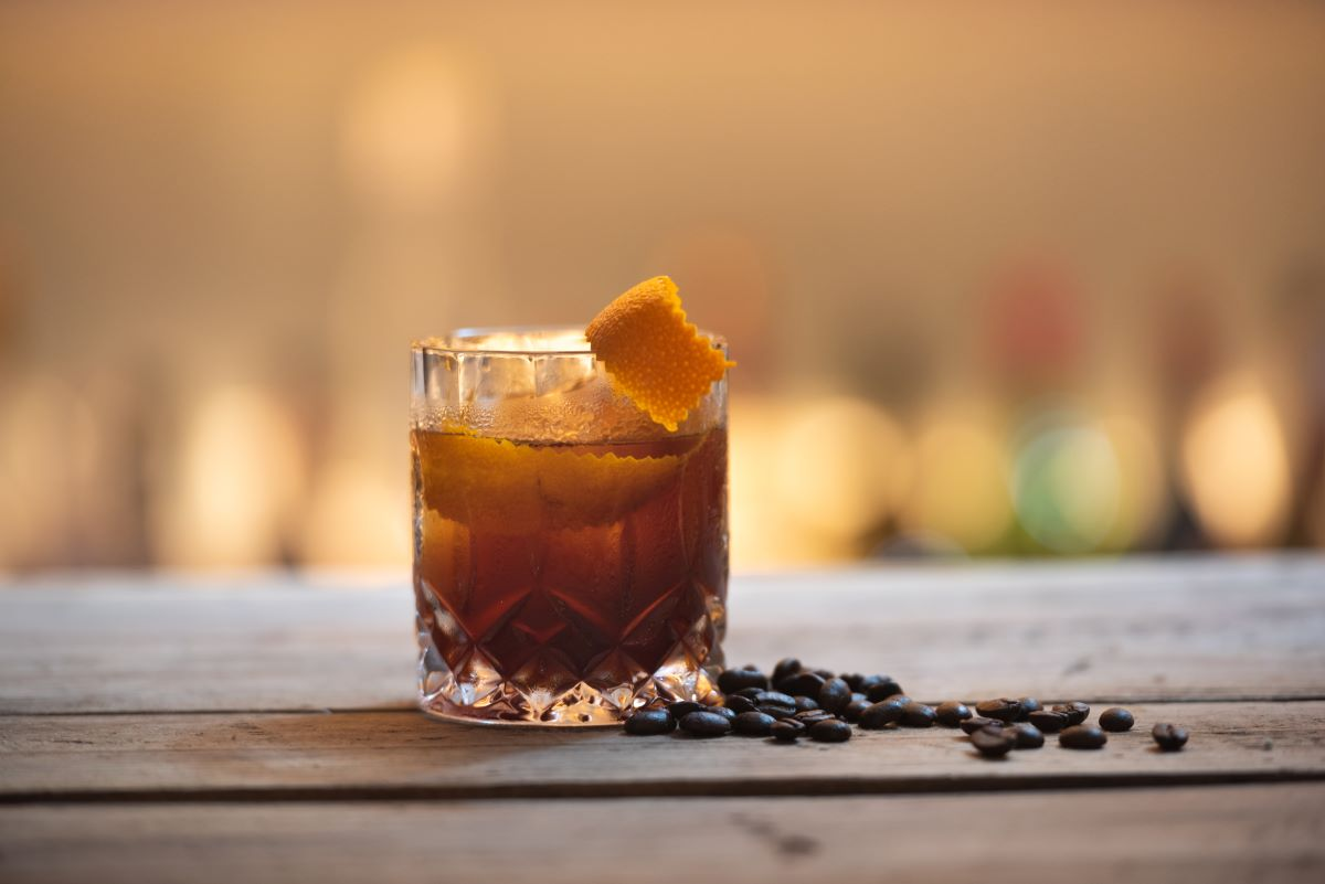 Crystal cut low ball with rum and and orange twist scattered on the right side of the glass are coffee beans on the wooden table