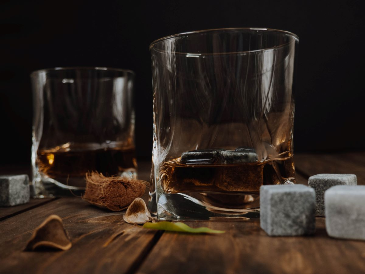Bourbon with stone whiskey rocks in low ball glasses with whiskey stones and leaf sitting on the wooden table near the glasses