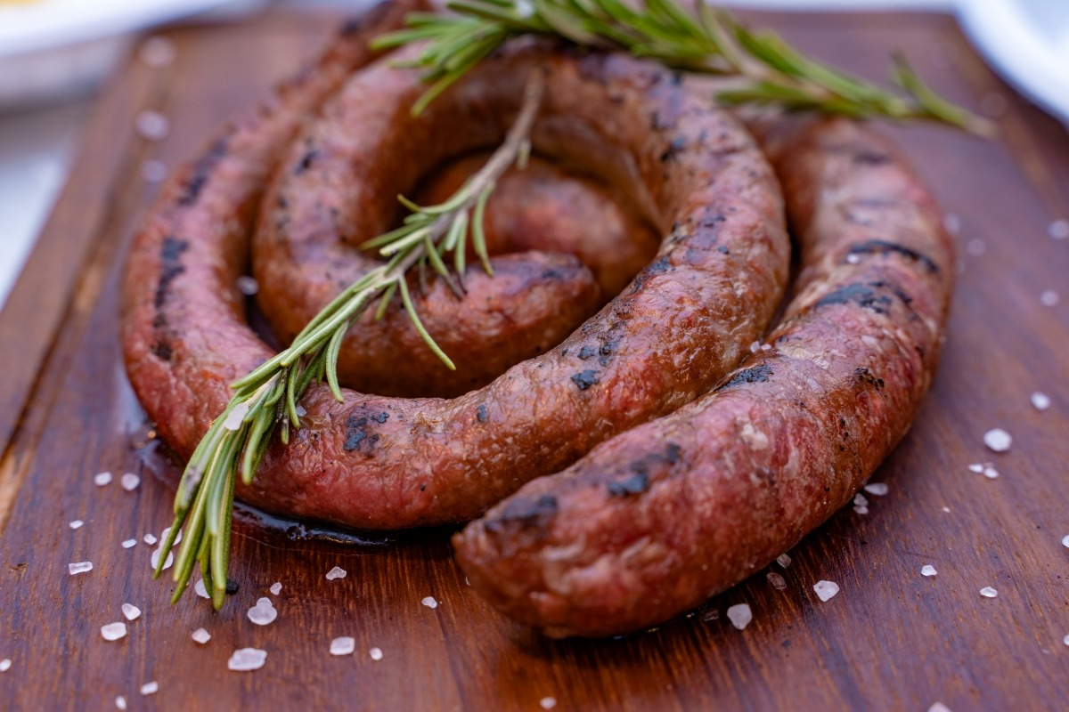 Sausage of the Month Clubs - Close up of a coiled grilled sausage on a wood cutting board with a couple of sprigs of rosemary sitting on top and coarse salt scattered around the cutting board