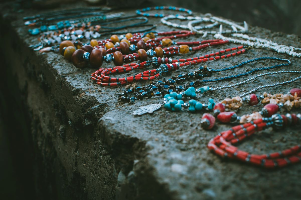 Beaded necklaces laying out on a stone wall
