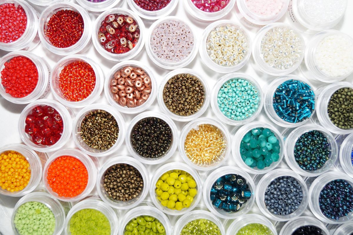 Bead of the Month Clubs - Round white containers of colorful beads in various shapes and cuts