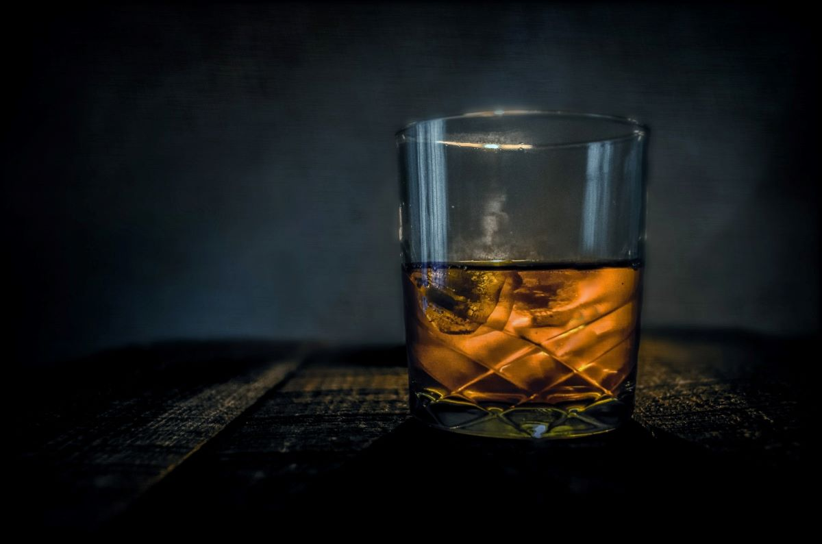 Chilled cut crystal low ball with scotch on the rocks on a wood table dim lighting