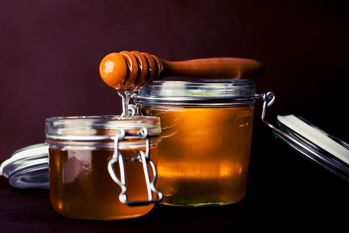 Honey of the Month Clubs - two short open jars with honey, with a wooden honey dipper resting on top dripping honey in the smaller of the two jars