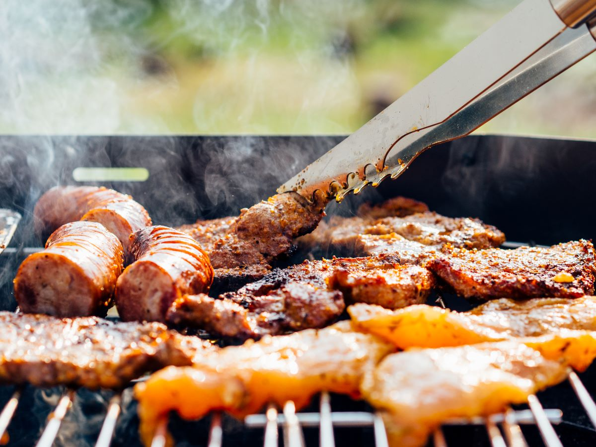 A grill with tongs turning meat. From left to right kielbasa pork and chicken both with a dry rub