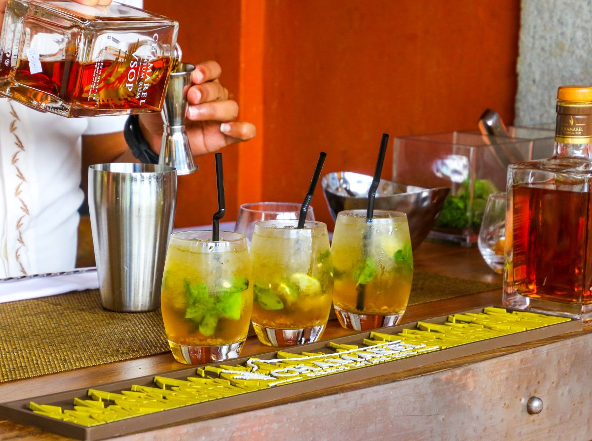 Bar with a bartender making rum drinks with mint and lime all three drinks are in oval shaped clear glasses with black straws