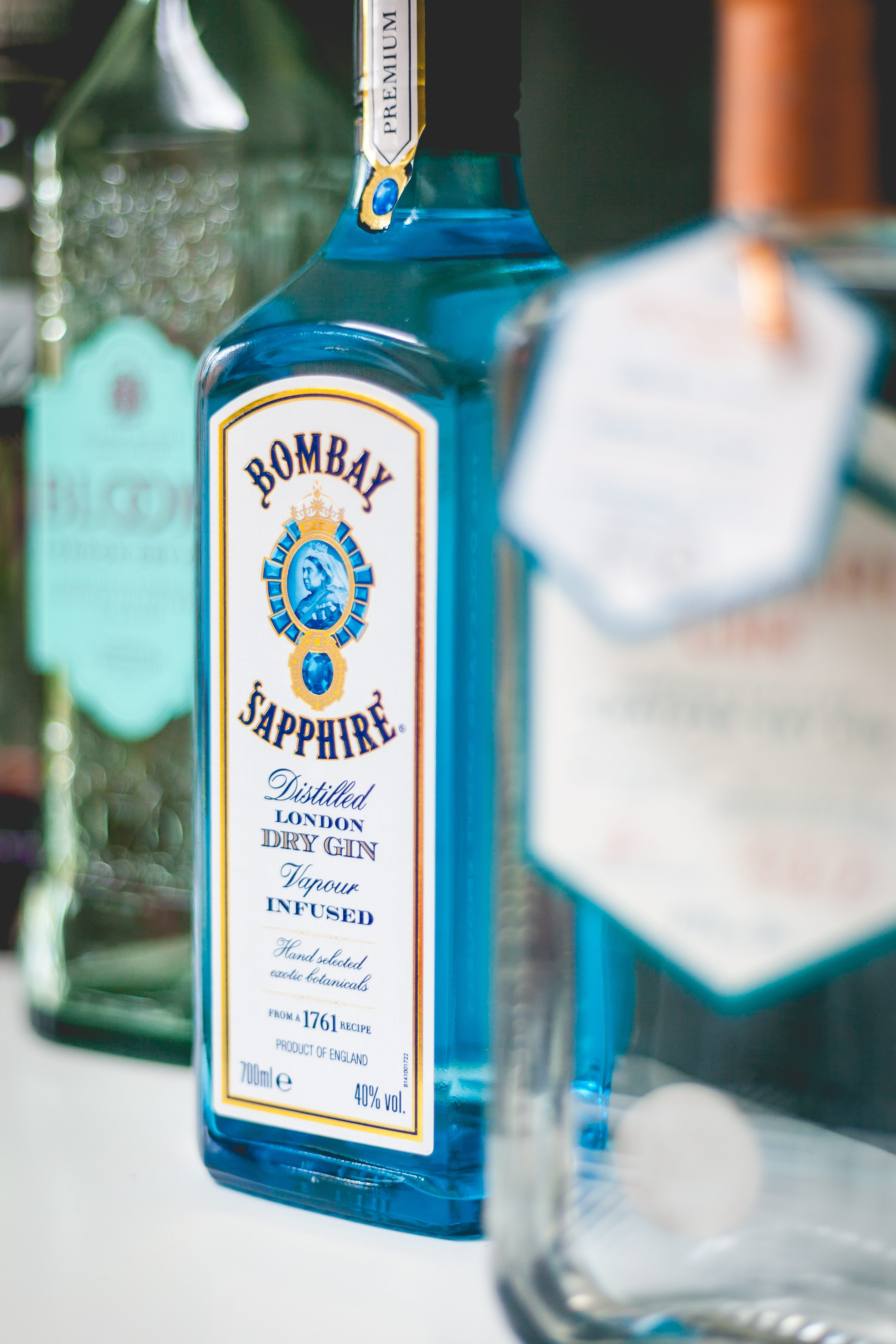 Bombay Sapphire Dry Gin Bottle with two other bottles on each side of the gin both out of focus