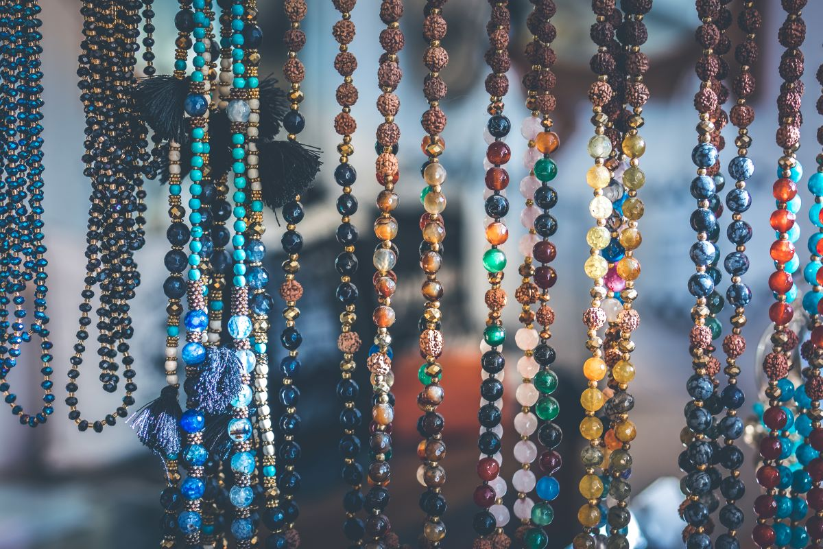Mulitple strands of earth tone beads hanging across the photo