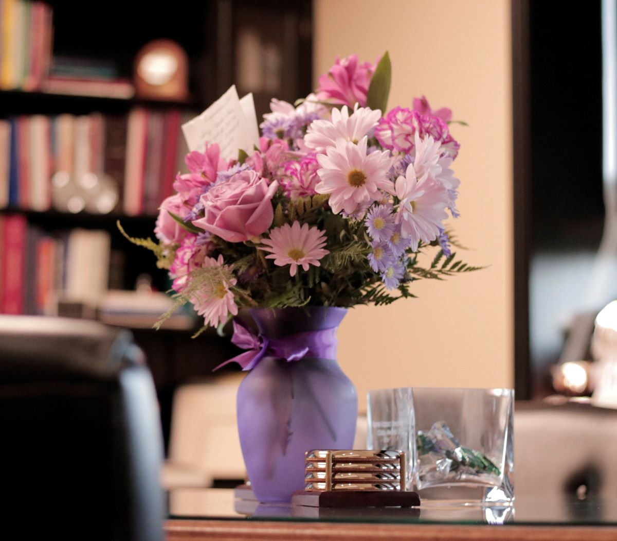 Flower of the Month Clubs - Lavender vase with purple bow containg roses, daisies, and other pink flowers with ferns with a card sticking out of the top of the pink and purple bouquet