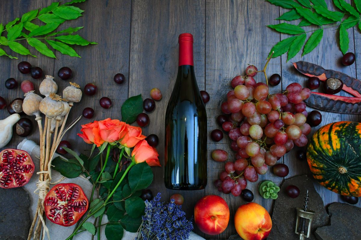 Red Wine Bottle Beside Grapes, Roses and Several Fruits on Brown Wooden Surface