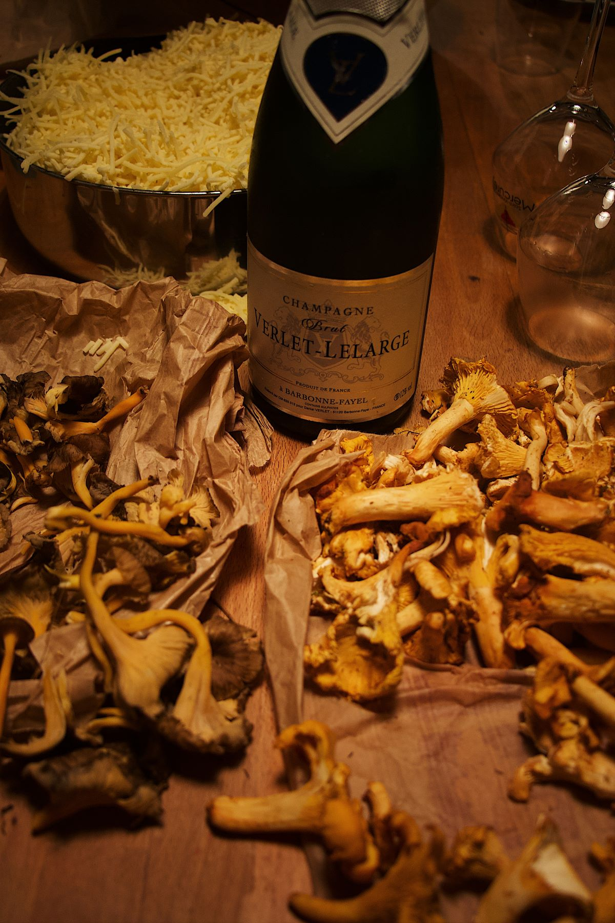 Various wild mushrooms arranged around a bottle of wine and wine glasses, some are laid out on brown parchment and some are in a bowl in the background