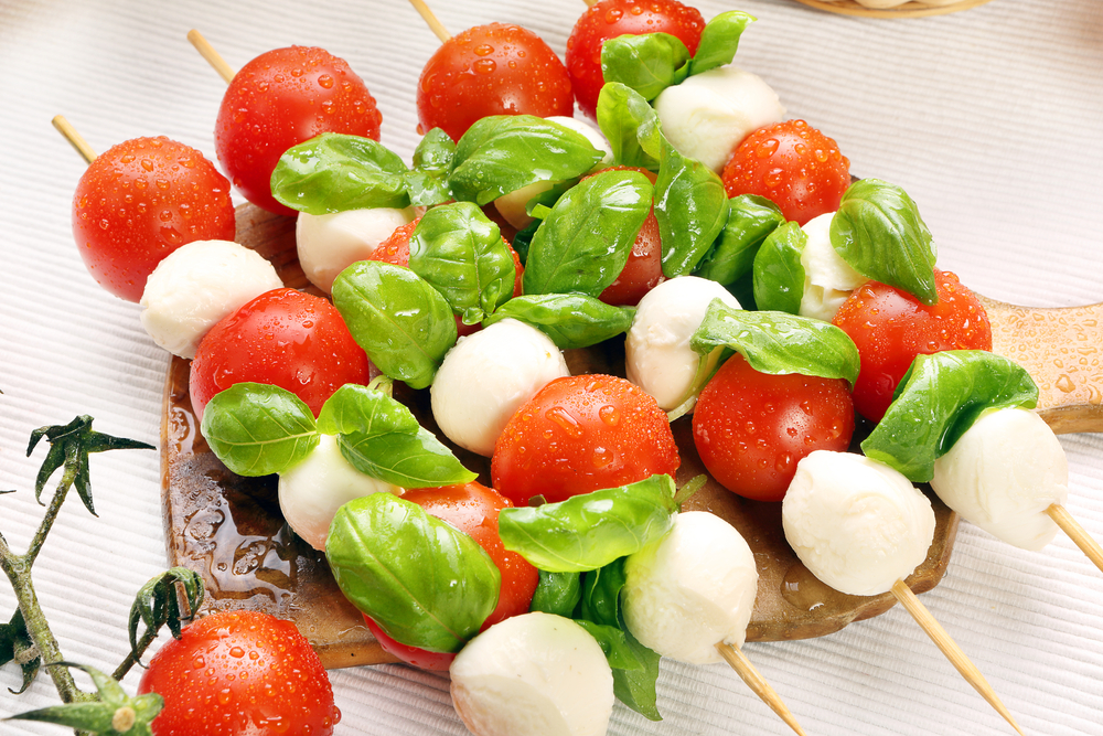 Long skewers with caprese salad ingredients threaded onto them