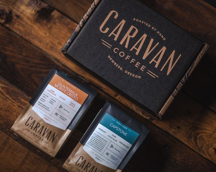 A black Caravan coffee box with two bags of coffee