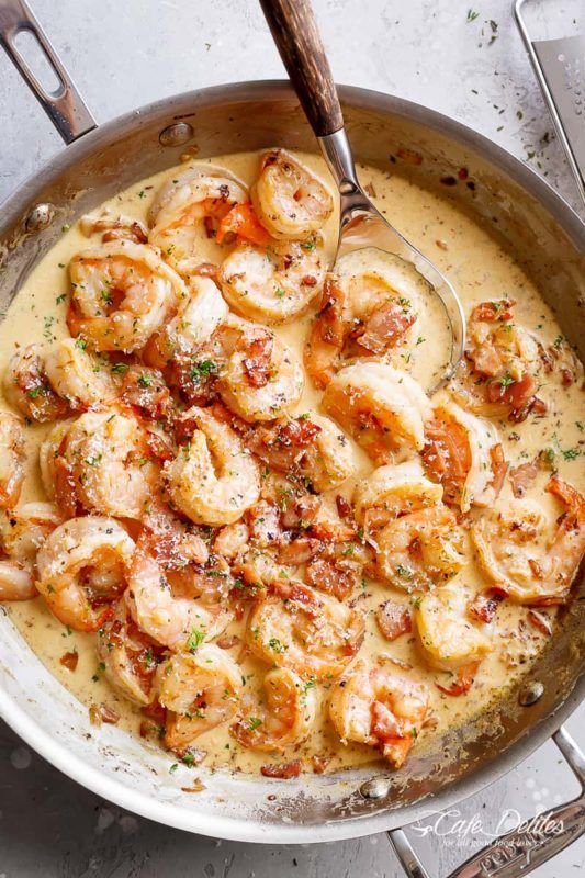 A frypan with shrimp and sauce