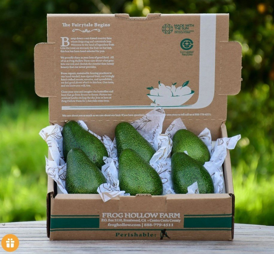 Card board box displayed outside with 6 green avocados displayed inside with tissue