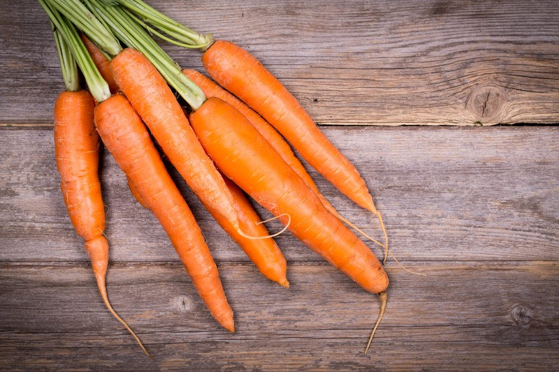 A bunch of seven orange carrots rests on a rustic wooden table.