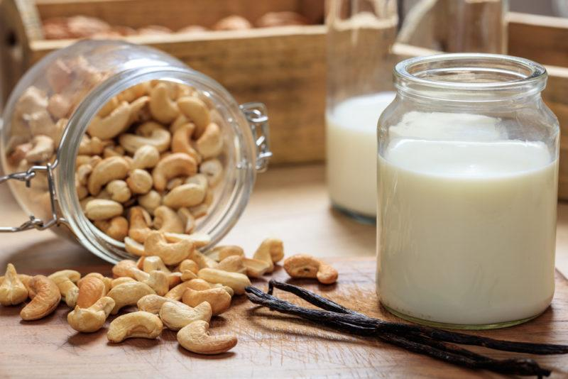 Two containers of cashew milk, with a jar filled of cashews spilling out
