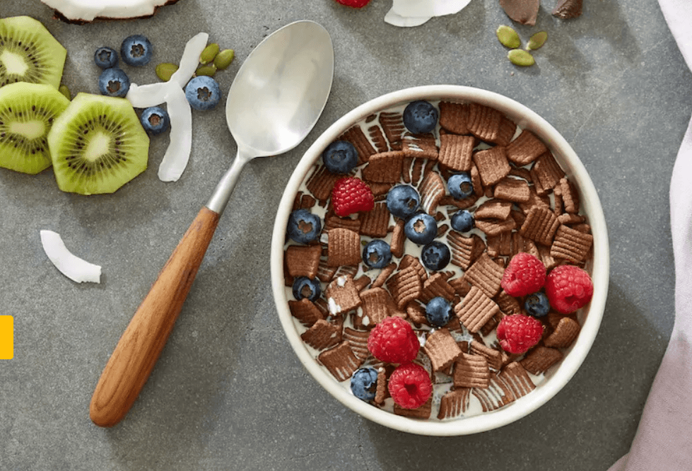 Bowl of cocoa square cereal with raspberries and blueberries with milk.  next to the bowl is a wooden handle spoon and various fruit and coconut scattered on the table near the bowl
