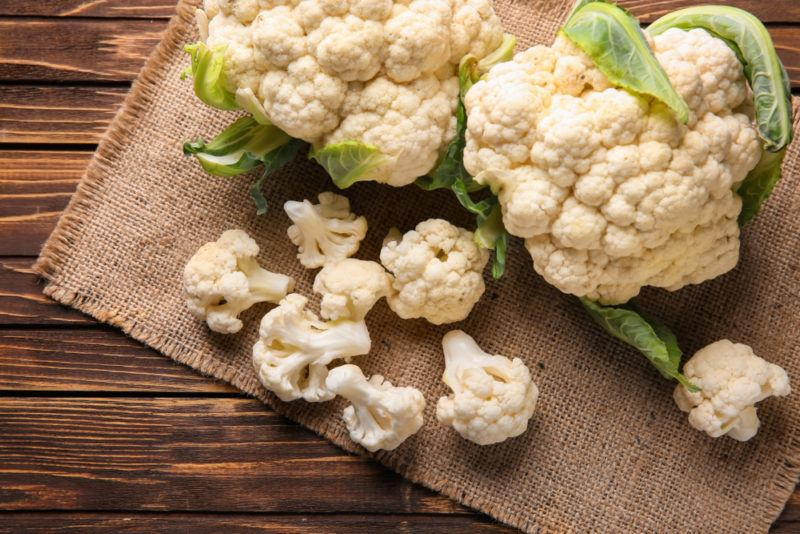 Raw cauliflower florets and a head of a cauliflower on a sack and a wooden table