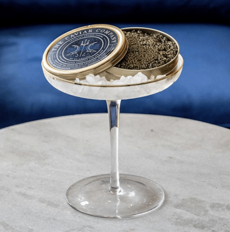 Round marble table with a champagne glass with ice and a tin of caviar resting on top of the crushed ice.  The tin is gold with a blue background