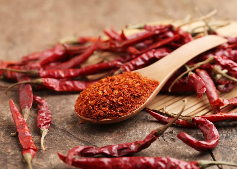 A spoonful of Cayenne pepper surrounded by dried cayenne peppers