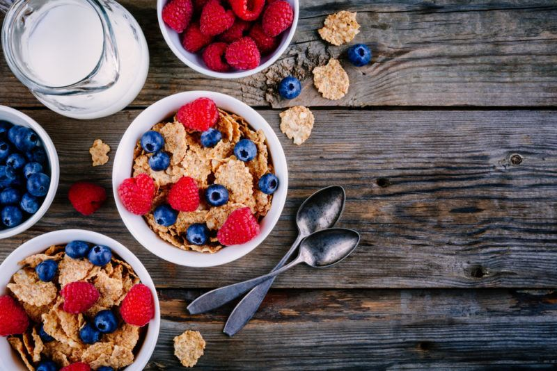 Two bowls of bran cereal on a wooden table, with milk and some fruit