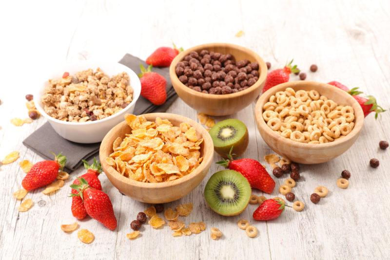 Four bowls of breakfast cereal with various fresh fruit on the table