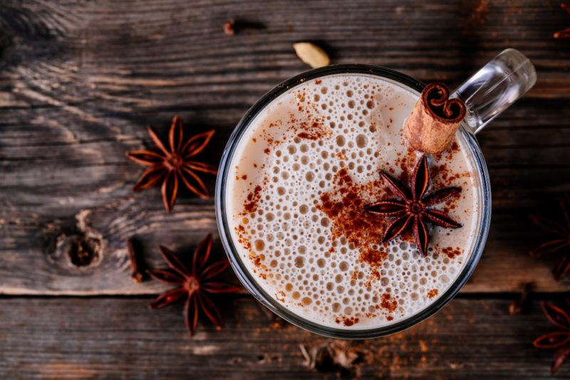 A top down image of a chai latte in a mug with various spices