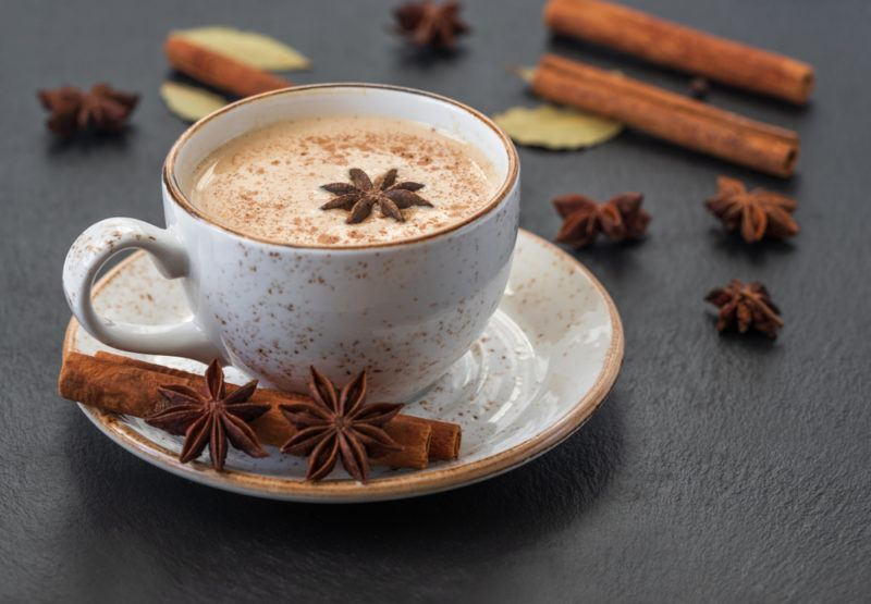 A mug of chai tea with cinnamon sticks and star anise on the saucer and the table