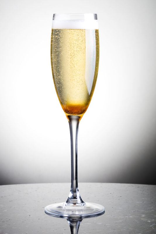 A Champagne Cocktail isolated against a white background
