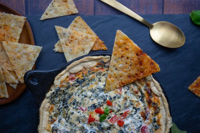 A dish with spinach dip and various taco chips