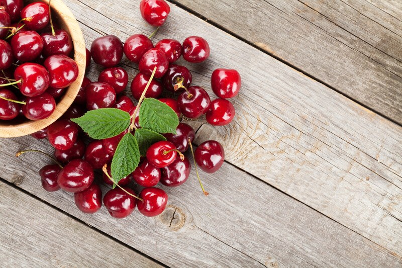 A bowl of dark red cherries and several loose cherries rest on a wooden table.
