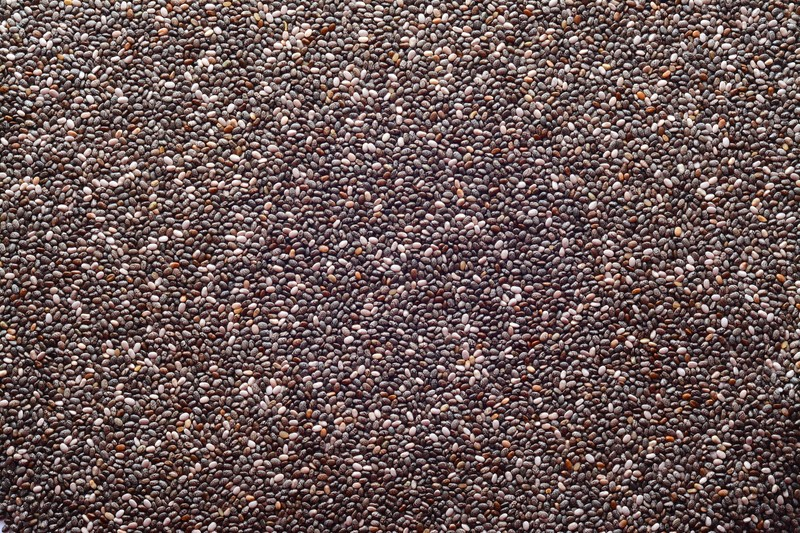 This photo shows an overhead view of chia seeds in black, gray, and white..