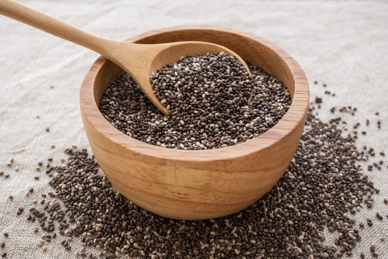 A brown bowl with a spoon of chia seeds