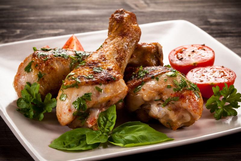 A white square plate with chicken drumsticks, greens and tomatoes