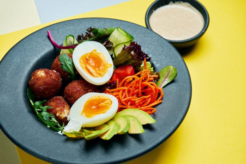 A blue plate with chicken croquettes, eggs and veggies