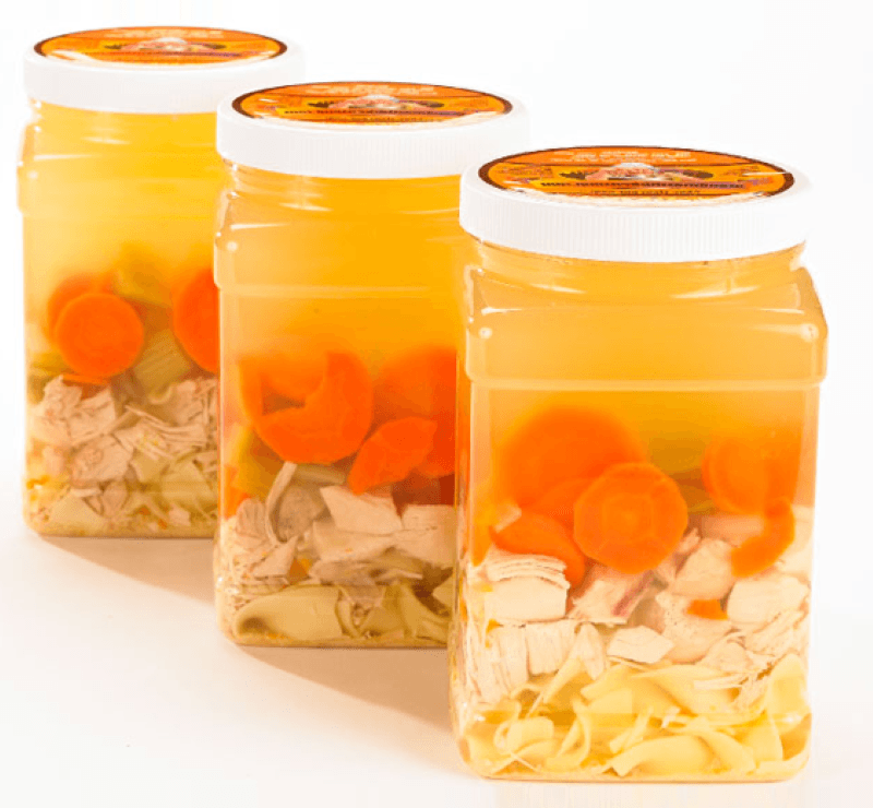 Three 1/2 gallon plastic containers with chicken noodle soup.  The covers of the jars have Grandma's Chicken Soup label on the top.
