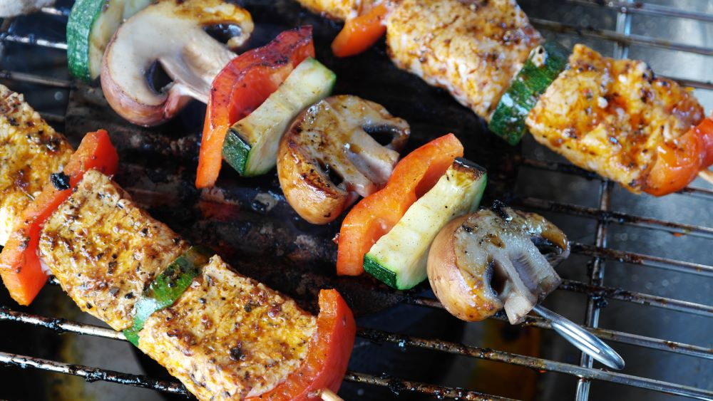 Chicken and Vegetable kabobs on a grill with a dry rub