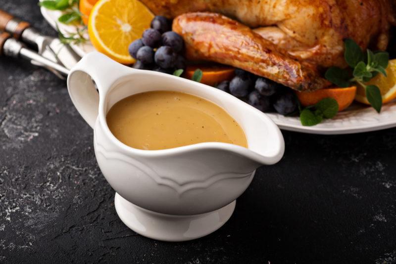 A gravy boat with chicken gravy next to a roast chicken