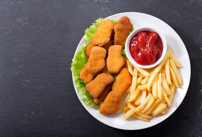 A white plate with processed chicken nuggets, tomato sauce, and fries