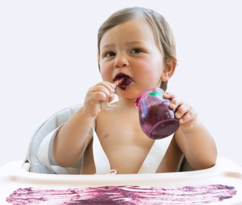 Baby sitting in high chair eating a purple baby food puree - baby food smeared all over the table top of the high chair