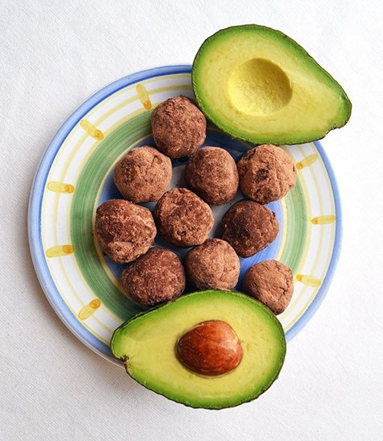 Round chocolate truffles on a plate with a halved avocado