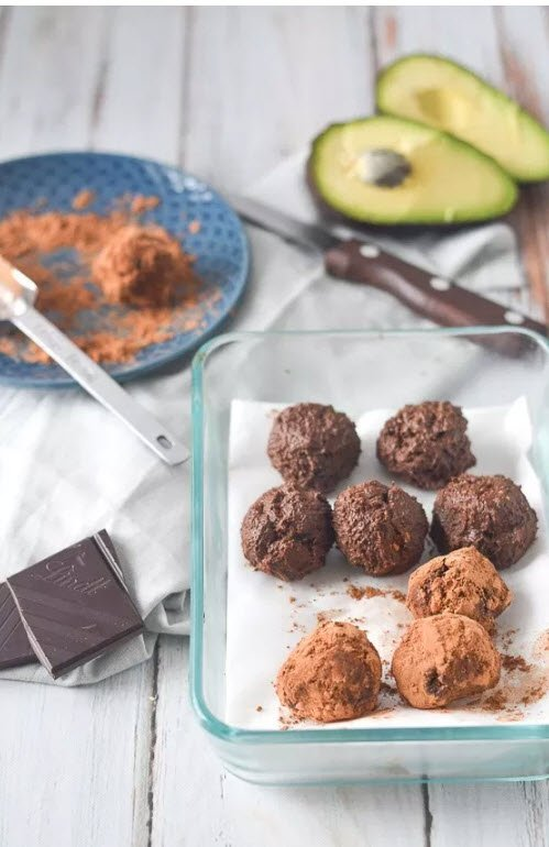 A selection of truffles in a glass tray, along with avocado and chocolate