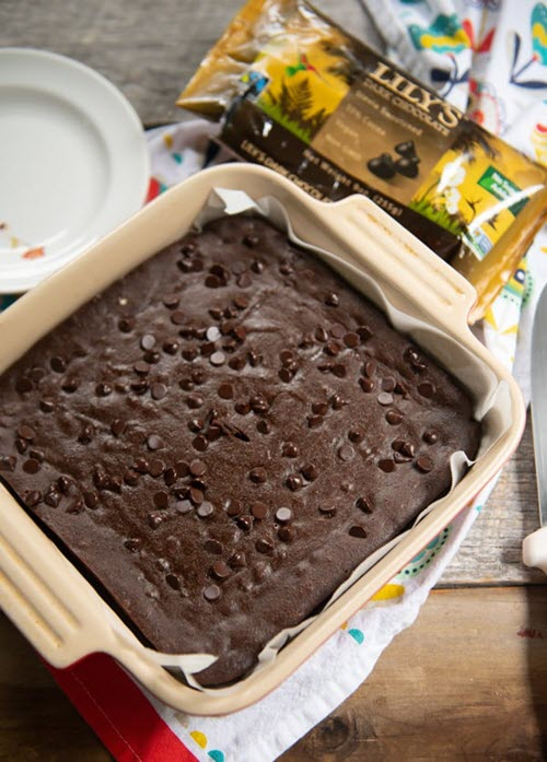 A container with a large chocolate brownie