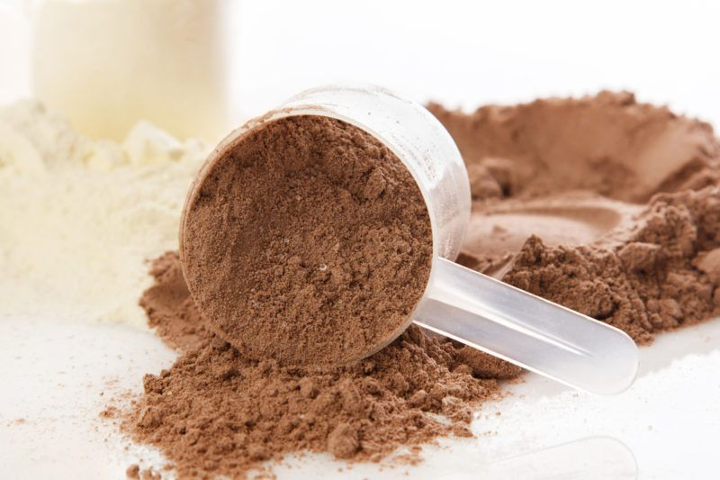 Chocolate and vanilla protein powder with scoops on a table