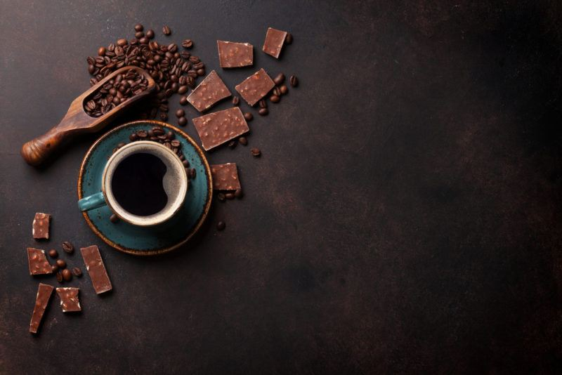 A mug of coffee, a scoop of coffee beans, and various pieces of chocolate with coffee
