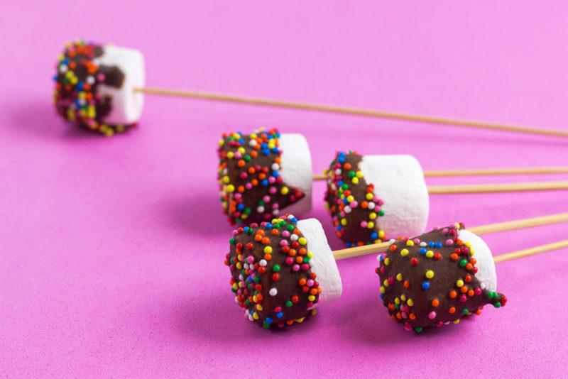A selection of marshmallows on sticks that have been dipped in chocolate and sprinkles