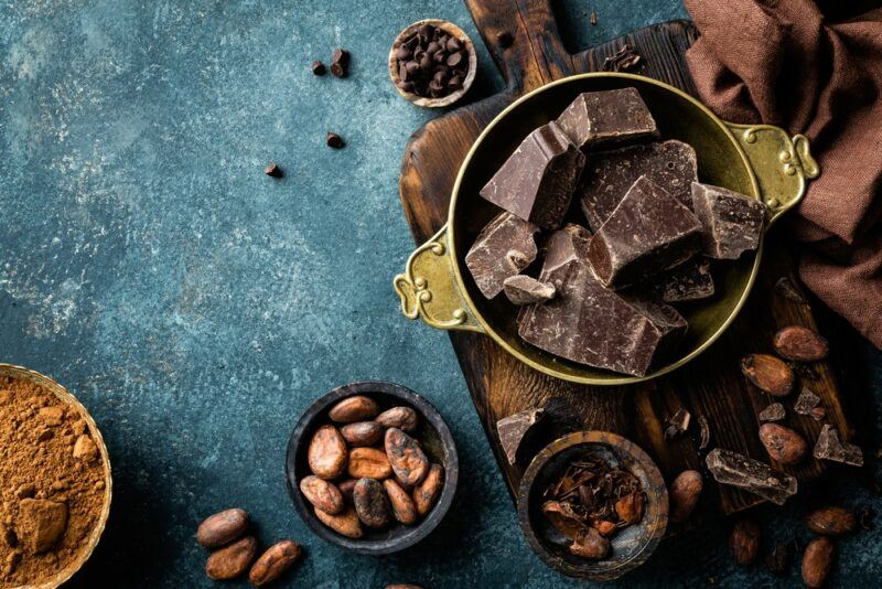 A blue table with a selection of bowls of dark chocolate and some cocoa powder