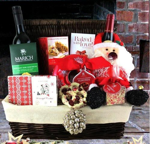 Large wicker basket containing various Christmas items and two bottles of wine